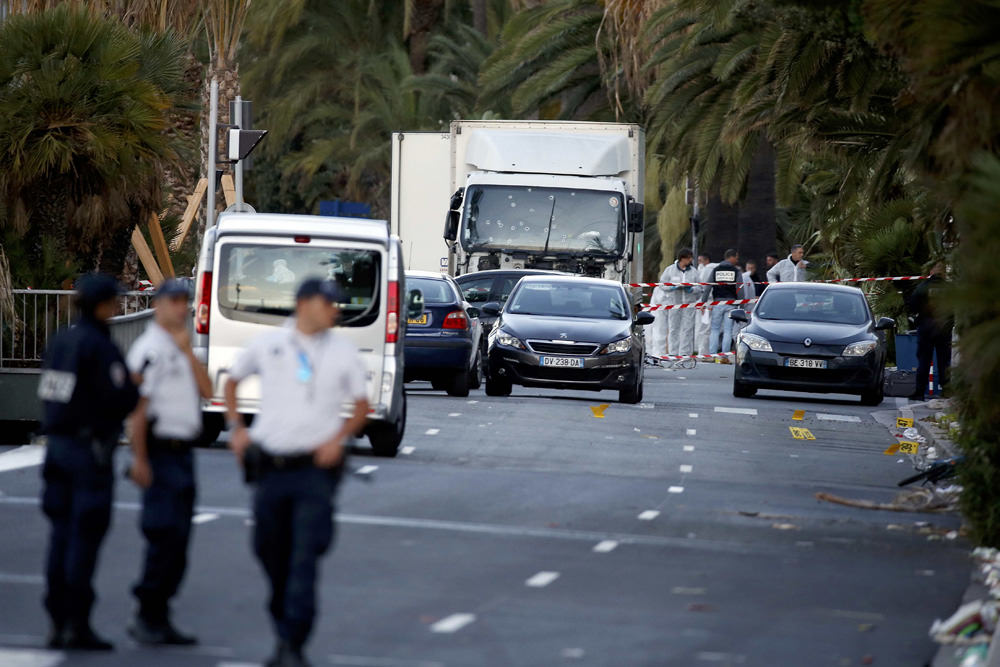 French police continue their investigation as they work near the heavy truck that ran into a crowd at high speed celebrating the Bastille Day July 14 national holiday on the Promenade des Anglais killing 80 people in Nice, France, July 15, 2016. REUTERS/Eric Gaillard ATTENTION EDITORS FRENCH LAW REQUIRES THAT VEHICLE REGISTRATION PLATES ARE MASKED IN PUBLICATIONS